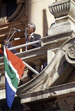 After the elections in 1994: Newly-elected President Nelson Mandela addressing the crowd from a balcony of the Townhall. UN Photo/Chris Sattlberger.